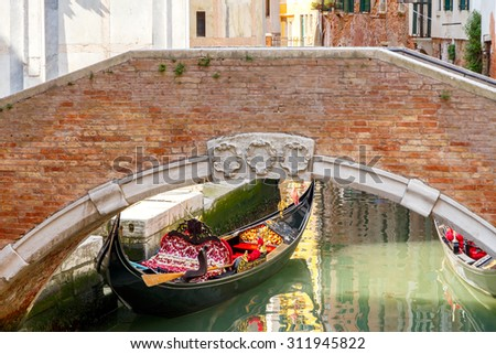 Traditional Venetian gondolas in one of the city's canals. - stock photo