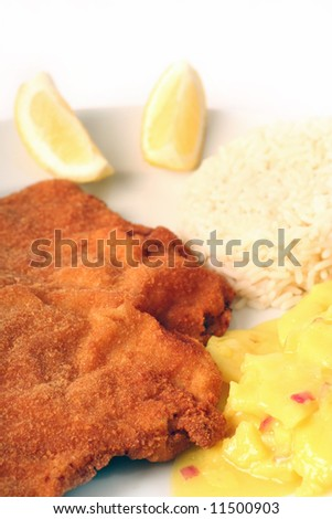 Traditional  viennese Schnitzel with potato salad and rice on a withe background.