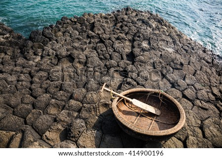 Traditional vietnamese boat on the basalt rocks formation, Da Dia Reef, Vietnam