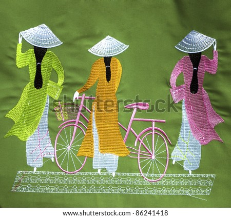 traditional Vietnamese particulars i.e. Ao Dai, hat and bicycle embroidered on a cloth as souvenir available for sale - stock photo