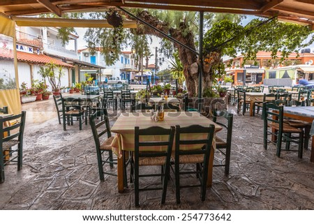 Traditional village eatery terrace with wooden tables and chairs under a huge tree - stock photo