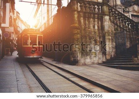 Traditional vintage tram makes its way across central streets in old city in sunny morning, public transport on metallic rails standing near architectural monument, electrical streetcar in urban scene - stock photo