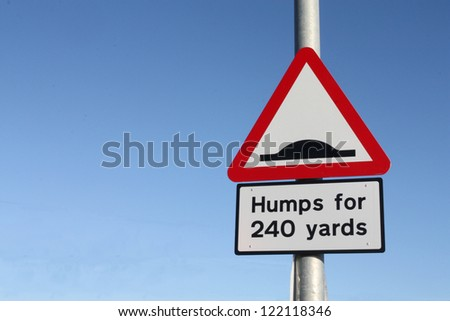 Traditional warning road sign for traffic calming road humps. - stock photo
