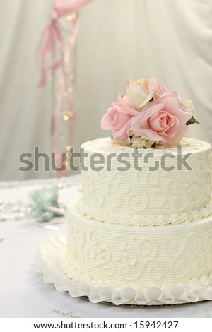 Traditional wedding cake with pink and cream rose cake topper. - stock photo