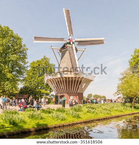 Traditional Windmill and Reflection in flower-park the Keukenhof Garden in Lisse full of Tourist people under Sunny Clear Blue Sky in Spring Season Springtime, the Netherlands - stock photo