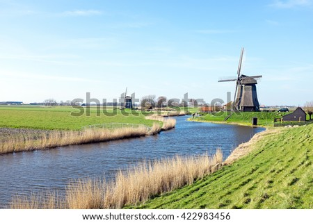 Traditional windmills in a dutch landscape in the Netherlands - stock photo