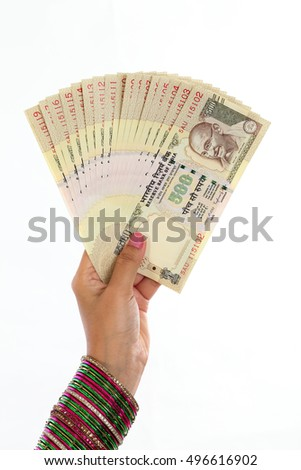 Traditional woman hand holding Indian five hundred rupee notes