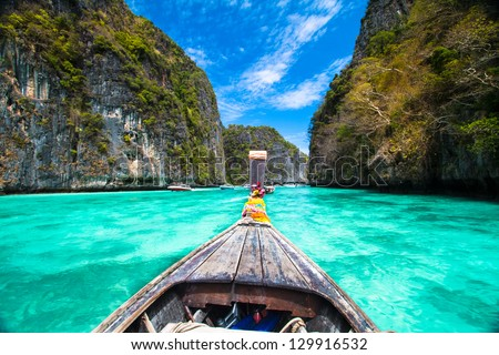 Traditional wooden  boat in a picture perfect tropical bay on Koh Phi Phi Island, Thailand, Asia. - stock photo