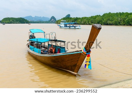 Traditional wooden decorated boat on tropical river with Krabi landmark (Khao Kanab Nam cliff) on background, Krabi Town, Thailand - stock photo
