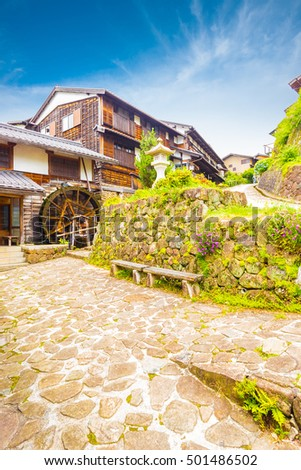 Traditional wooden houses and waterwheel line the stone path on this beautifully restored section of the historic Edo-period Nakasendo road in station town of Magome, Japan. Vertical