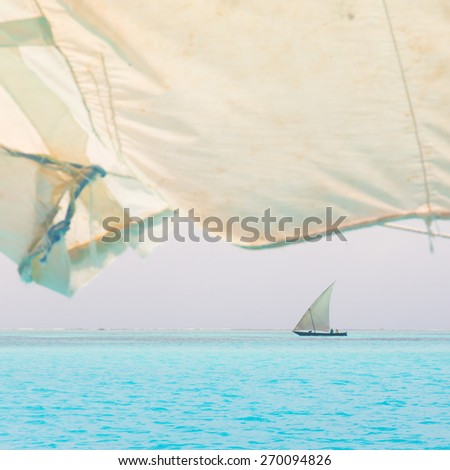 Traditional wooden sailboat sailing on a horizon of turquoise blue sea of Zanzibar, Tanzania, Afrika. - stock photo