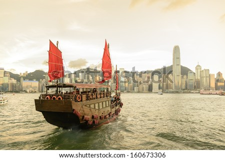 Traditional wooden sailboat / tourist junk sailing in Victoria Harbour during sunset ,Hong Kong - stock photo
