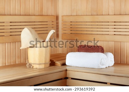 Traditional wooden sauna for relaxation with bucket of water and set of clean towels - stock photo