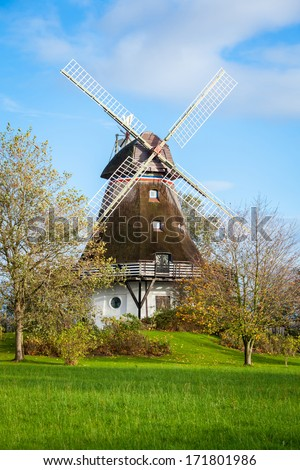 Traditional wooden windmill in a lush garden with four sails or blades turning in the wind to generate power and energy for farming or manufacture from the kinetic energy of the wind - stock photo