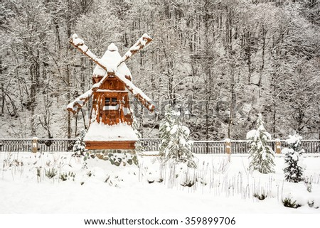 Traditional wooden windmill under the caps of snow with a stone basement standing near the fence along the hill with high trees during the snowfall - stock photo