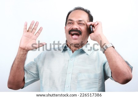 Traditionally dressed happy Indian man speak loudly over mobile phone - stock photo