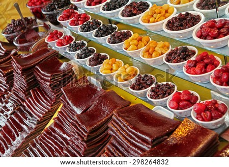 Traditionally dried and processed forest fruit strips and small bowls of sour plums, sour cherries and forest fruits to be sold in Darakeh and Darband recreational quarters of Tehran, Iran. - stock photo