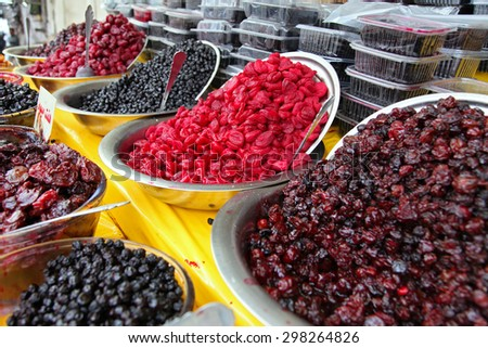 Traditionally dried and processed sour plums, sour cherries and forest fruits presented in large bowls to be sold in Darakeh and Darband recreational quarters of Tehran, Iran. - stock photo
