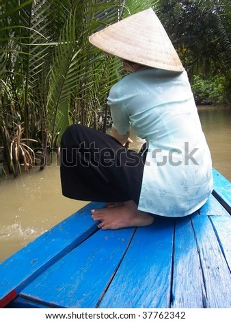 traditonal Vietnam woman with conical hat going down mekong delta on boat