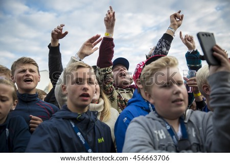Traena, Norway - July 07 2016: audience of fans cheering at concert of Norwegian singer Astrid S at Traenafestivalen, music festival taking place on the small island of Traena