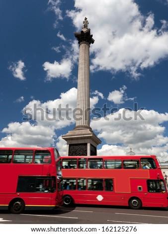 Trafalgar Square in London, the UK. Red buses in motion - stock photo