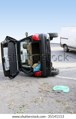 Traffic accident black car roll over side - stock photo