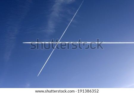 Traffic: airliners criss-crossing the blue sky. - stock photo