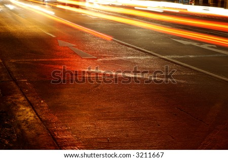 Traffic Arrow sign on the road at night. Slow Shutter Speed. - stock photo