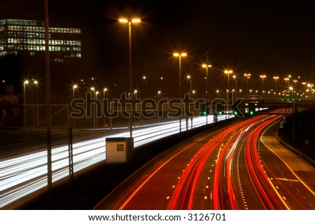 Traffic at full speed on a busy highway in the evening