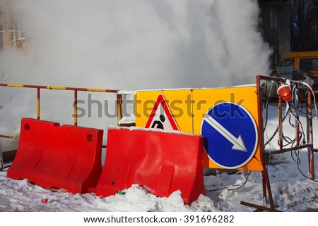 Traffic barriers and road signs at steaming heat pipeline damage in the winter - stock photo