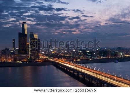 Traffic blurs across a bridge on the Han River as dusk settles in over Seoul, South Korea. - stock photo
