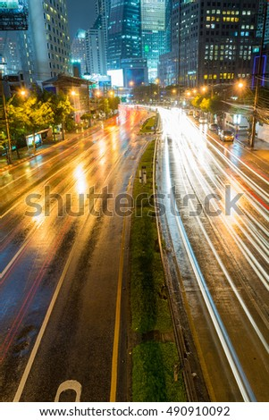Traffic congestion .Lights and illumination reflection during the heavy rain. Commercial, modern building and night in Bangkok, Thailand city center.