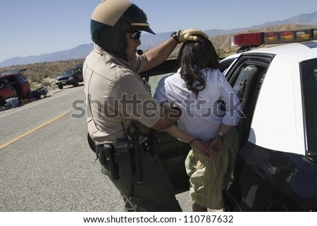Traffic cop arresting young female drunken driver - stock photo