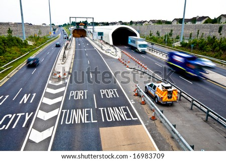 Traffic entering and exiting road tunnel - stock photo