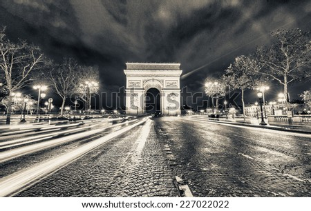 Traffic flow in Paris. Car light trails in front of Arc de Triomphe. - stock photo