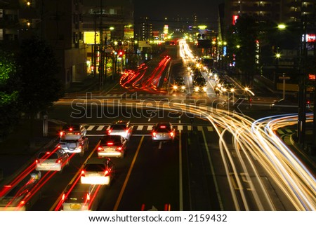 Traffic in a city crossroad during the night. - stock photo