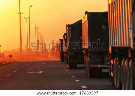 Traffic Jam of Heavy Trucks in Sunset - stock photo