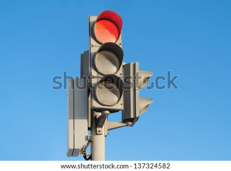 Traffic light against the blue sky with burning red signal