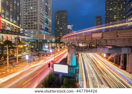 Traffic light and sky train in busy light trails at night - Bangkok, Thailand