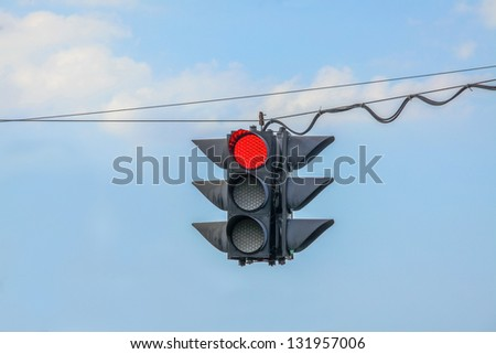 Traffic light on red hanging on wires in the air - stock photo