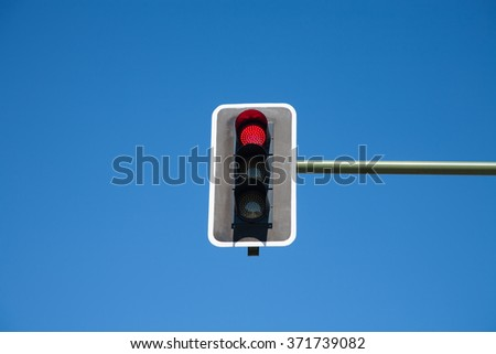 traffic light semaphore red light on orange and green lights off  in green pole on blue sky horizontal - stock photo