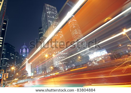 traffic light trails in the street by modern building - stock photo