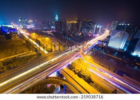 traffic light trails on overpass and cityscape at night - stock photo