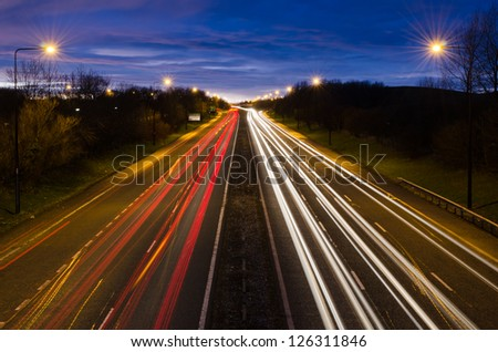 Traffic light trails out of Newcastle / Traffic light trails leaving Newcastle at dusk - stock photo