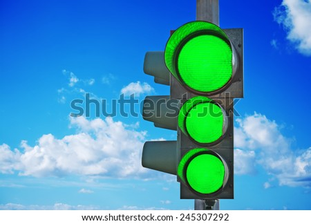 traffic light with three green lights on under a blue sky - stock photo