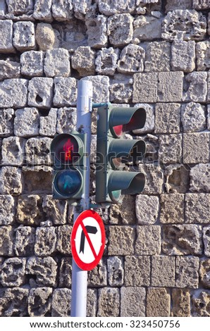 Traffic lights against old stone wall in Rhodes, Greece - stock photo