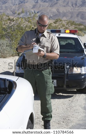 Traffic officer in uniform writing ticket - stock photo