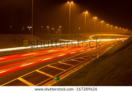 Traffic on a highway with streetlights at night. Long exposure.