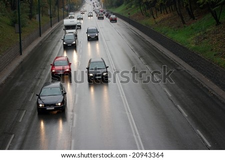 Traffic on a wet road after rain - stock photo