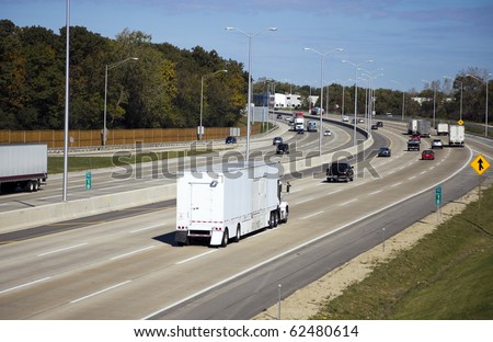 Traffic on Highway - horse transporter in the foreground. - stock photo